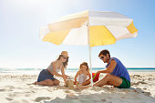 Shot of a young family building a sandcastle under an umbrella