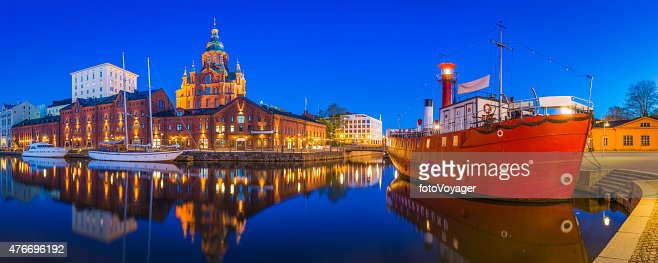 Helsinki Uspenski Cathedral overlooking tranquil waterfront harbour illuminated dusk Finland