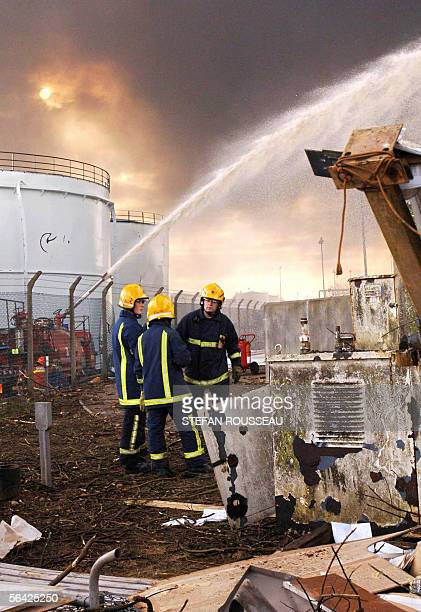Firefighters monitor foam being poured onto burnt oil storage tanks at the Buncefield oil depot in Hemel Hempstead on the outskirts of London 13...