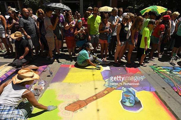 Hemingway left helps her sister Juliette middle finish her BB King inspired chalk art during the 14th annual chalk art festival on June 5 2016 in...