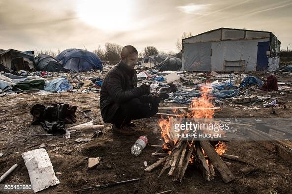 Hemn a Kurd migrant keeps warm next to a fire on a makeshift camp known as 'the jungle' on January 18 2016 in Calais The residents of the camp in the...