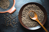 Hemp seeds on a plate and in a sieve on a gray blue stone horizontal