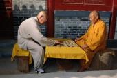 Henan in Shaolin China Two contemplative monks Shi Yong Po and Shi Yan Shan are playing xia qi Chinese chess outside their cells Shi Yong Po reports...