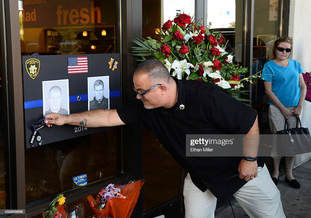 Henderson Police Department Marshal Peter Gariano of Nevada places a magnetic ribbon on a poster with the images of the police officers that were killed, on the window of CiCi's Pizza during a vigil outside the restaurant on June 9, 2014 in Las Vegas, Nevada. The Las Vegas Metropolitan Police Department says officers Alyn Beck and Igor Soldo were shot and killed yesterday at the restaurant by Jerad Miller and his wife Amanda Miller. Police say the Millers then went into a nearby Wal-Mart where Amanda Miller killed Joseph Wilcox before the Millers killed themselves.