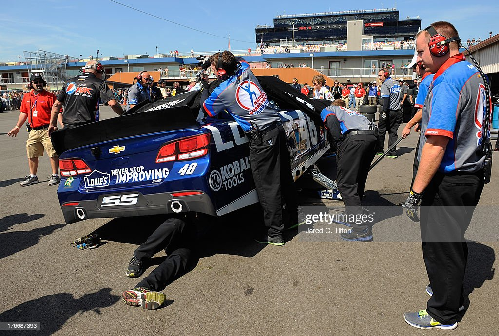 Hendrick team members work on the damaged car of Jimmie Johnson (not pictured), driver of the #48 Lowe's Chevrolet, after an incident during practice for the NASCAR Sprint Cup Series 44th Annual Pure Michigan 400 at Michigan International Speedway on August 17, 2013 in Brooklyn, Michigan.