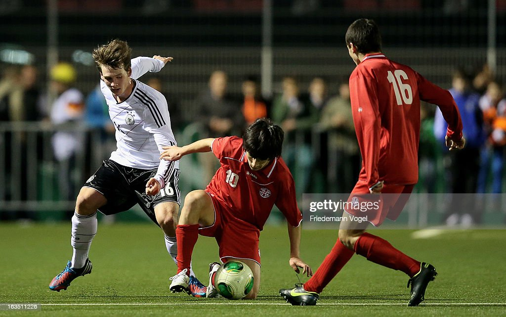Hendrik Hofgaertner (L) of Germany and Giorgi Beridze (C) of Georgia battle for the ball during the U17 International Friendly match between Germany and Georgia at Toennies-Arena on March 6, 2013 in Rheda-Wiedenbruck, Germany.