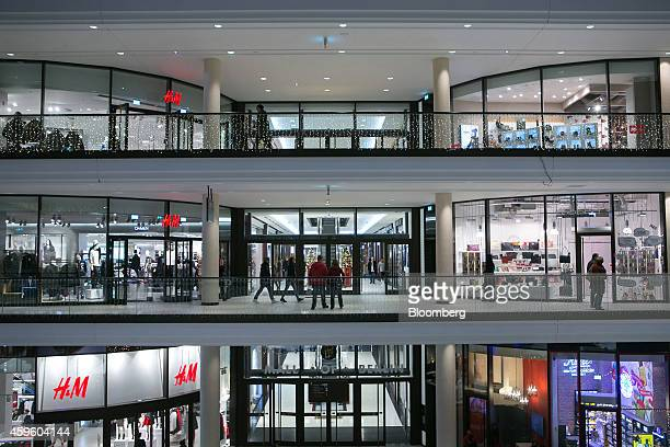 A Hennes Mauritz AB store left stands illuminated as customers walk on multiple floors inside the Mall of Berlin operated by High Gain House...