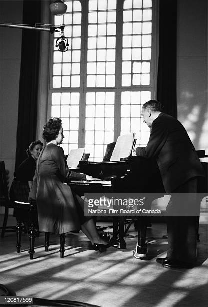 Henri Gagnon Canadian composer organist and music educator is standing next to a female student during a piano rehearsal at the Conservatoire de...