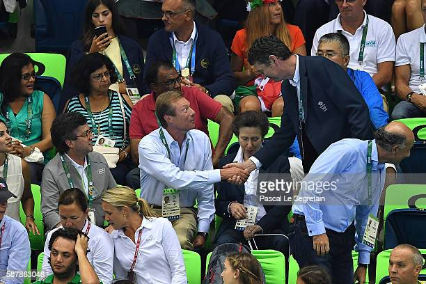 Henri Grand Duke of Luxembourg shakes hands with Sir Timothy Laurence as Princess Anne sits during women's 200m Individual medley on Day 4 of the Rio...