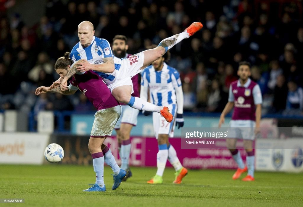 Henri Lansbury of Aston Villa is challenged by Aaron Mooy of Huddersfield Town during the Sky Bet Championship match between Huddersfield Town and Aston Villa at the John Smith's Stadium on March 07, 2017 in Huddersfield, England.