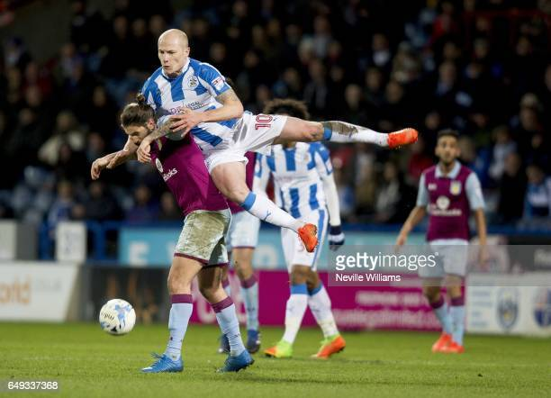 Henri Lansbury of Aston Villa is challenged by Aaron Mooy of Huddersfield Town during the Sky Bet Championship match between Huddersfield Town and...