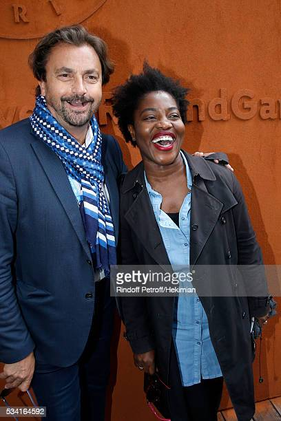 Henri Leconte and humorist Claudia Tagbo attend the 2016 French Tennis Open Day Four at Roland Garros on May 25 2016 in Paris France