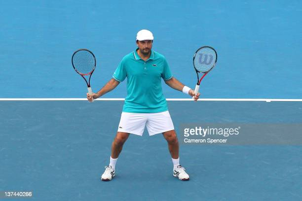 Henri Leconte of France holds two racquets during his legends match with partner Guy Forget of France against Darren Cahill of Australia and Richard...