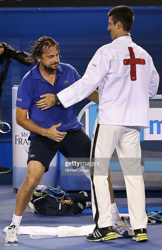 Henri Leconte of France is revived by Novak Djockovic impersonating a doctor during the legends doubles match with Guy Forget of France against Pat Cash of Australia and Goran Ivanisevic of Croatia during the 2013 Australian Open at Melbourne Park on January 24, 2013 in Melbourne, Australia.