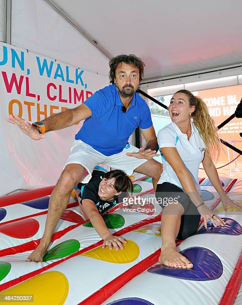 Henri Leconte of France poses with Hockey player Claire Messent and Surfer Nikki van Dijk during a game of giant inflatable twister on Grand Slam...