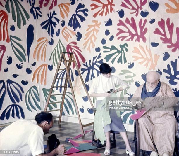 Henri Matisse In Nice Henri MATISSE assis dans un fauteuil roulant découpant des morceaux de papiers de couleurs avec son assistante dans son atelier...