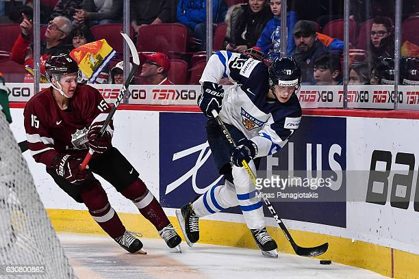 Henrik Borgstrom of Team Finland skates the puck past Tomass Zeile of Team Latvia during the 2017 IIHF World Junior Championship relegation game at...