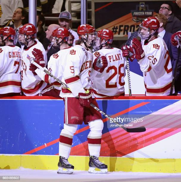 Henrik Borgstrom of the Denver Pioneers is congratulated by teammates after scoring in the first period against the Notre Dame Fighting Irish during...