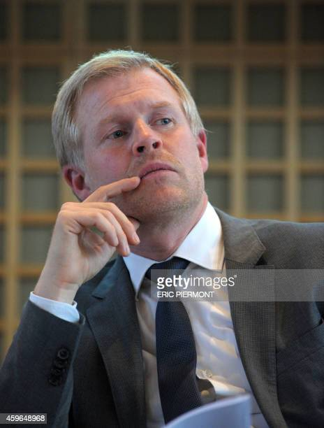 Henrik Enderlein head of the Jacques Delors Institute in Berlin listens during a press conference with French Economy Minister Emmanuel Macron German...