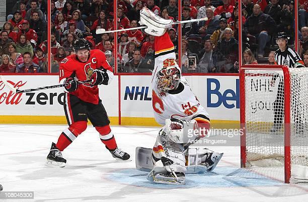 Henrik Karlsson of the Calgary Flames makes a blocker save as Daniel Alfredsson of the Ottawa Senators positions himself outside the crease at...