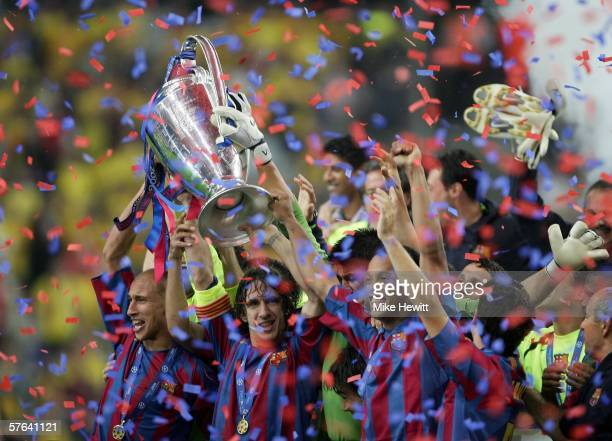 Henrik Larsson Carles Puyol and Ronaldinho of Barcelona lift the trophy with celebrating team mates after they win the UEFA Champions League Final...