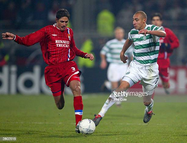Henrik Larsson of Celtic is tackled by Edmilson of Lyon during the UEFA Champions League Group A match between Olympique Lyonnais and Celtic at...