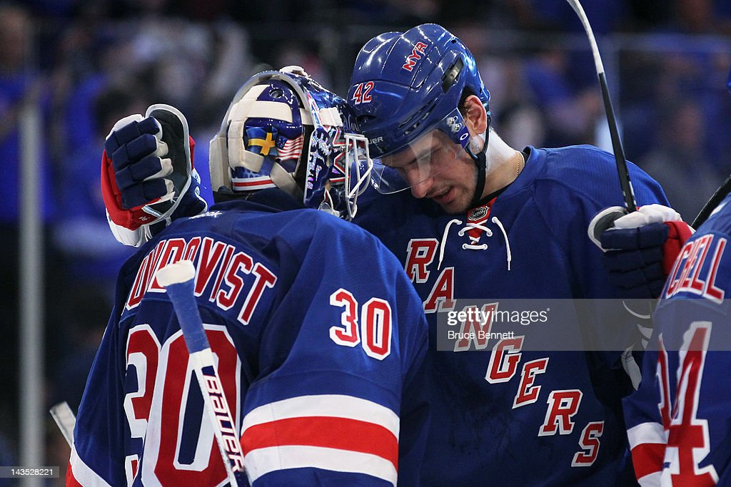 <a gi-track='captionPersonalityLinkClicked' href=/galleries/search?phrase=Henrik+Lundqvist&family=editorial&specificpeople=217958 ng-click='$event.stopPropagation()'>Henrik Lundqvist</a> #30 and <a gi-track='captionPersonalityLinkClicked' href=/galleries/search?phrase=Artem+Anisimov&family=editorial&specificpeople=543215 ng-click='$event.stopPropagation()'>Artem Anisimov</a> #42 of the New York Rangers celebrate their 3 to 1 win over the Washington Capitals in Game One of the Eastern Conference Semifinals during the 2012 NHL Stanley Cup Playoffs at Madison Square Garden on April 28, 2012 in New York City.