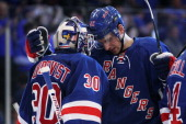 Henrik Lundqvist and Artem Anisimov of the New York Rangers celebrate their 3 to 1 win over the Washington Capitals in Game One of the Eastern...
