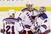 Henrik Lundqvist Artem Anisimov and Derek Stepan of the New York Rangers celebrate their 3 to 0 win over the New Jersey Devils in Game Three of the...