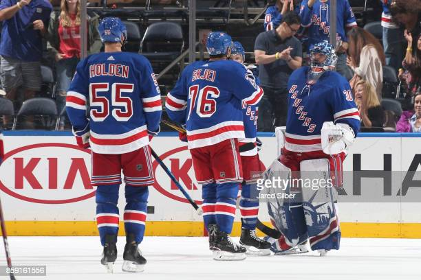 Henrik Lundqvist Brady Skjei and Nick Holden of the New York Rangers celebrate after defeating the Montreal Canadiens 20 at Madison Square Garden on...