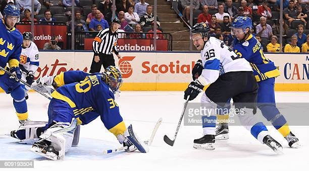 Henrik Lundqvist makes a save with Nicklas Backstrom of Team Sweden and Jussi Jokinen of Team Finland battling in front during the World Cup of...