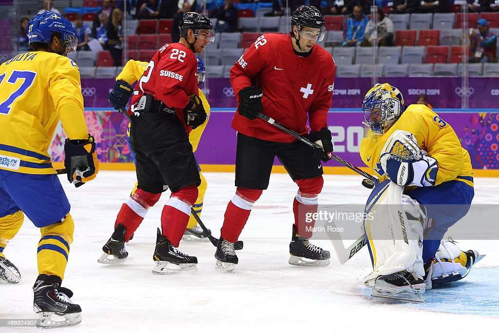 <a gi-track='captionPersonalityLinkClicked' href=/galleries/search?phrase=Henrik+Lundqvist&family=editorial&specificpeople=217958 ng-click='$event.stopPropagation()'>Henrik Lundqvist</a> #30 of Sweden makes a save against <a gi-track='captionPersonalityLinkClicked' href=/galleries/search?phrase=Nino+Niederreiter&family=editorial&specificpeople=6667732 ng-click='$event.stopPropagation()'>Nino Niederreiter</a> #22 and <a gi-track='captionPersonalityLinkClicked' href=/galleries/search?phrase=Simon+Moser&family=editorial&specificpeople=7727793 ng-click='$event.stopPropagation()'>Simon Moser</a> #82 of Switzerland in the first period during the Men's Ice Hockey Preliminary Round Group C game on day seven of the Sochi 2014 Winter Olympics at Bolshoy Ice Dome on February 14, 2014 in Sochi, Russia.
