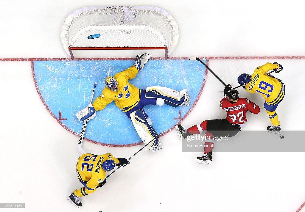 Henrik Lundqvist of Sweden makes a save against Nino Niederreiter of Switzerland in the first period during the Men's Ice Hockey Preliminary Round...