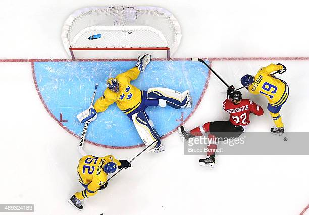 Henrik Lundqvist of Sweden makes a save against Nino Niederreiter of Switzerland in the first period during the Men's Ice Hockey Preliminary Round...