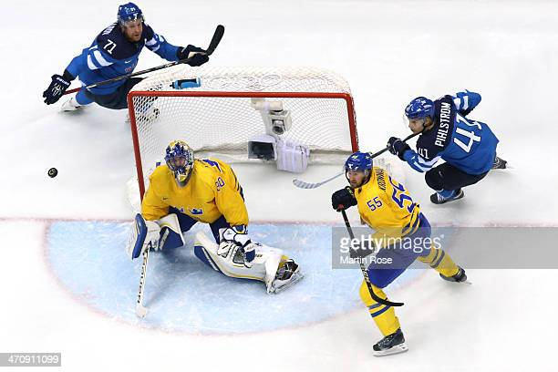 Henrik Lundqvist of Sweden tends the net against Leo Komarov and Antti Pihlstrom of Finland during the Men's Ice Hockey Semifinal Playoff on Day 14...
