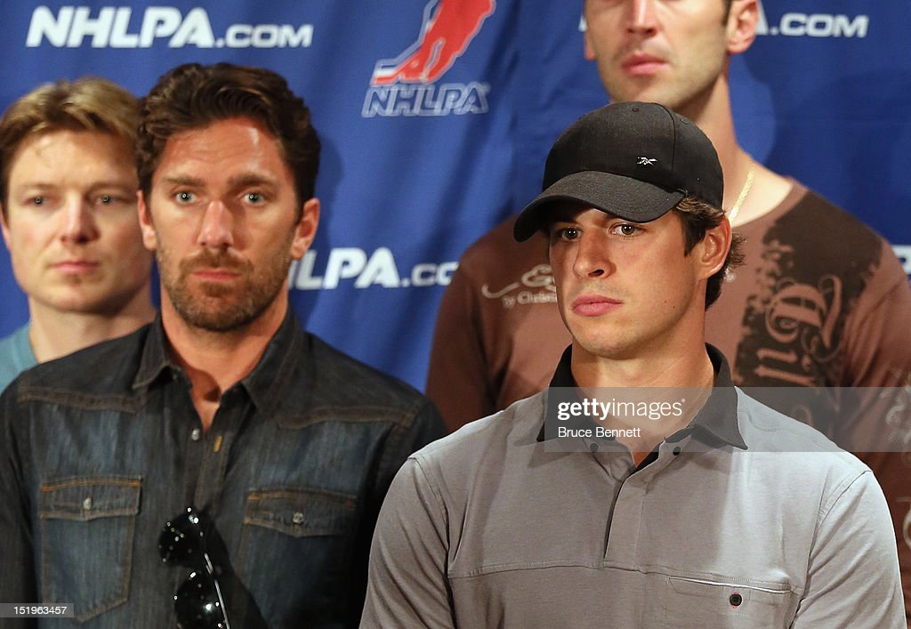 Henrik Lundqvist of the New York Rangers and Sidney Crosby of the Pittsburgh Penguins listen to the NHLPA press conference at Marriott Marquis Times Square on September 13, 2012 in New York City.