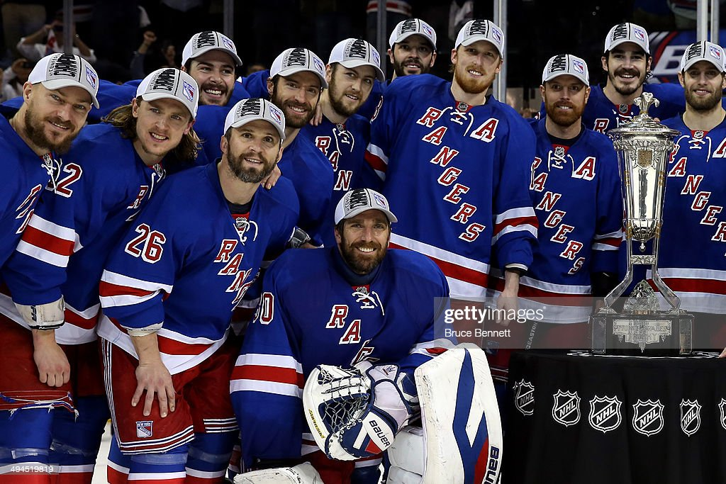 Henrik Lundqvist of the New York Rangers and the rest of the team pose with the Prince of Wales Trophy after defeating the Montreal Canadiens in Game...