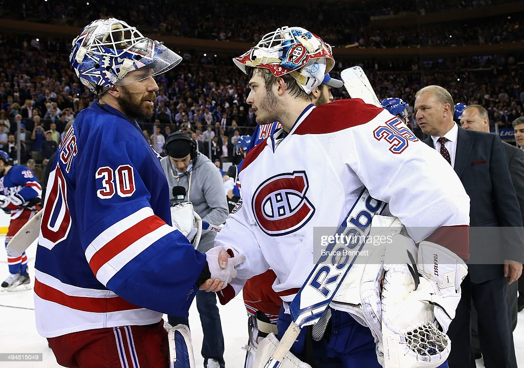 Henrik Lundqvist of the New York Rangers ashakes hands with Dustin Tokarski of the Montreal Canadiens after winning Game Six to advance to the...