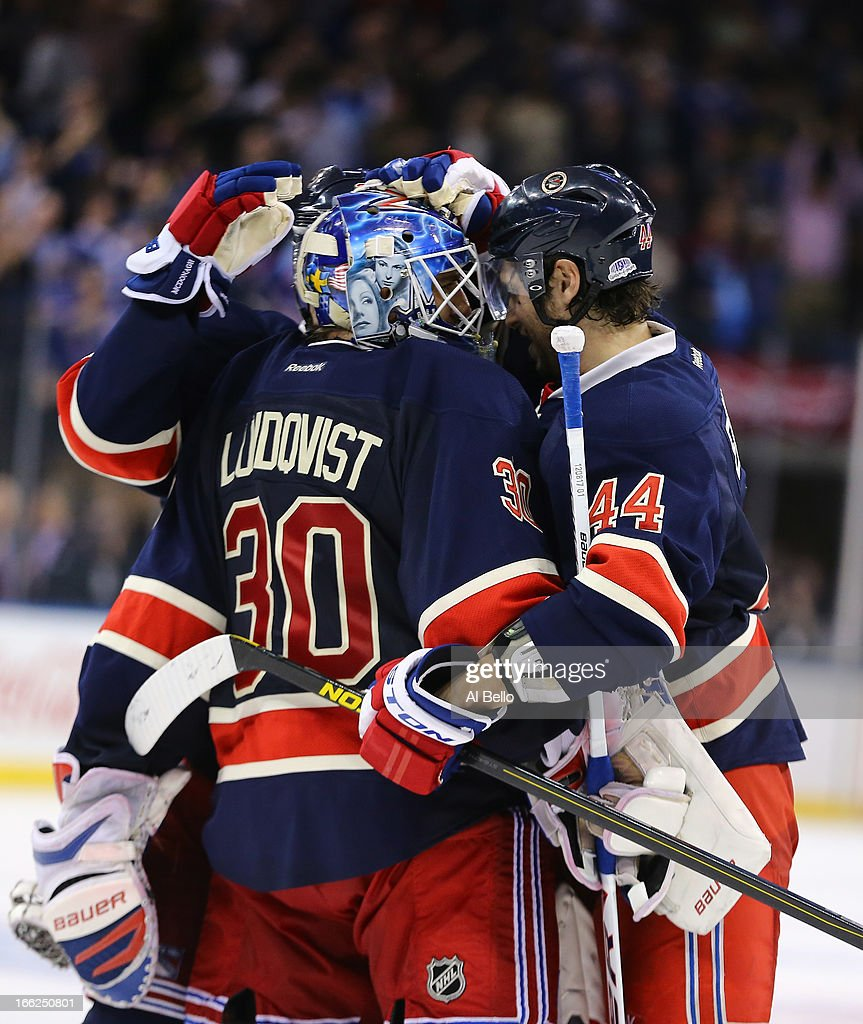 Henrik Lundqvist of the New York Rangers celebrates a 32 shootout win against the Toronto Maple Leafs with Ryan McDonagh and Steve Eminger of the New...
