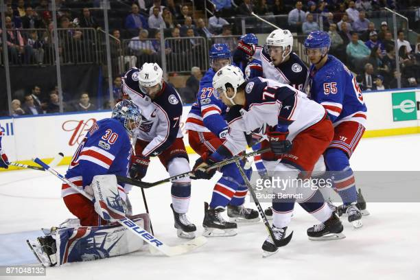 Henrik Lundqvist of the New York Rangers covers the puck as Josh Anderson of the Columbus Blue Jackets looks for the rebound at Madison Square Garden...