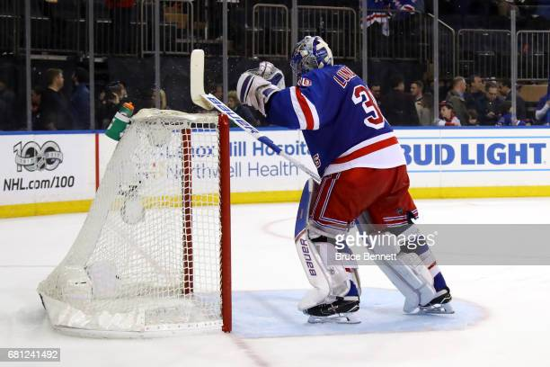 Henrik Lundqvist of the New York Rangers cracks his stick over the cross bar after JeanGabriel Pageau of the Ottawa Senators scored an open net goal...