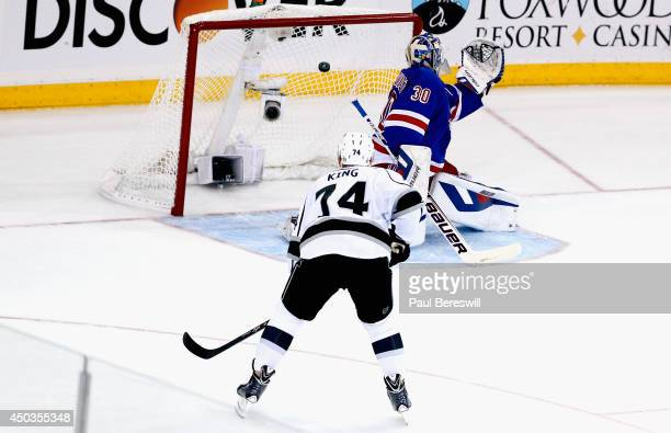Henrik Lundqvist of the New York Rangers gives up a goal to Jeff Carter of the Los Angeles Kings with Dwight King of the Los Angeles Kings looking on...