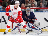 Henrik Lundqvist of the New York Rangers is screened by Daniel Cleary of the Detroit Red Wings at Madison Square Garden on January 16 2014 in New...