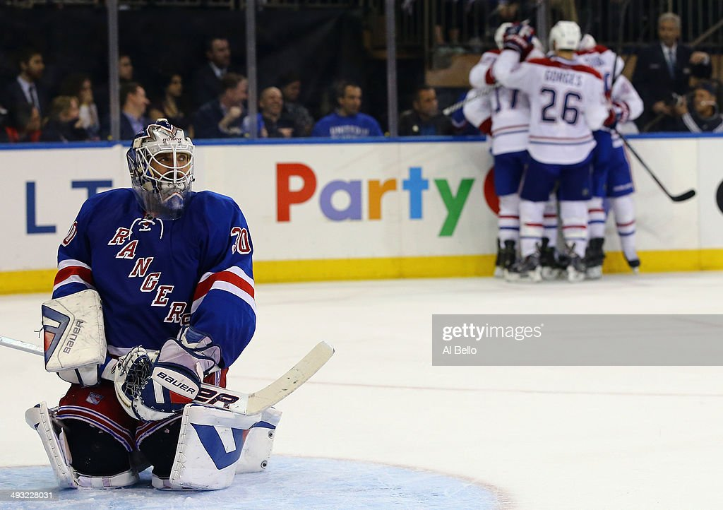 Henrik Lundqvist of the New York Rangers looks on as Daniel Briere of the Montreal Canadiens celebrates his third period goal in Game Three of the...