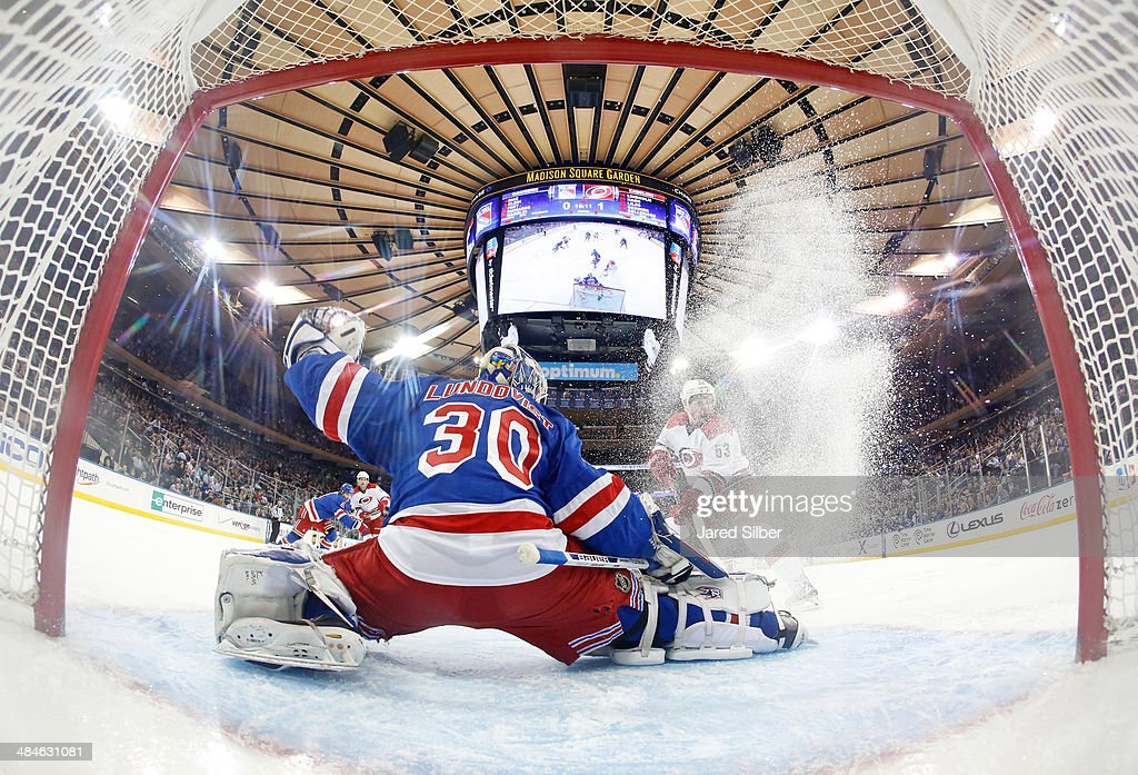 <a gi-track='captionPersonalityLinkClicked' href=/galleries/search?phrase=Henrik+Lundqvist&family=editorial&specificpeople=217958 ng-click='$event.stopPropagation()'>Henrik Lundqvist</a> #30 of the New York Rangers makes a pad save as <a gi-track='captionPersonalityLinkClicked' href=/galleries/search?phrase=Jeff+Skinner&family=editorial&specificpeople=3147596 ng-click='$event.stopPropagation()'>Jeff Skinner</a> #53 of the Carolina Hurricanes crashes the net at Madison Square Garden on April 08, 2014 in New York City. The New York Rangers won 4-1.
