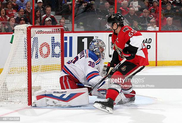 Henrik Lundqvist of the New York Rangers makes a save against Erik Karlsson of the Ottawa Senators in overtime during an NHL game at Canadian Tire...