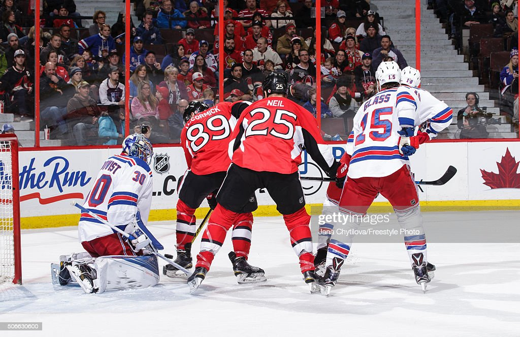 Henrik Lundqvist of the New York Rangers makes a save against Max McCormick and Chris Neil of the Ottawa Senators as Tanner Glass of the New York...