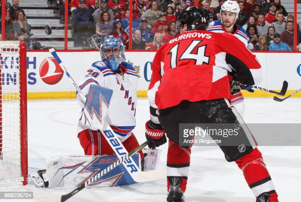 Henrik Lundqvist of the New York Rangers makes a save as Alexandre Burrows of the Ottawa Senators and Brendan Smith look on at Canadian Tire Centre...