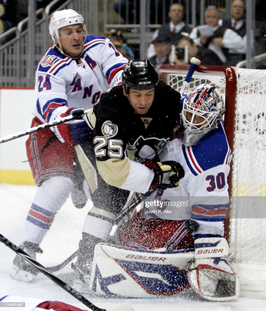 Henrik Lundqvist #30 of the New York Rangers makes a save as Maxime Talbot #25 of the Pittsburgh Penguins is checked by Ryan Callahan #24 at Consol Energy Center on March 20, 2011 in Pittsburgh, Pennsylvania.