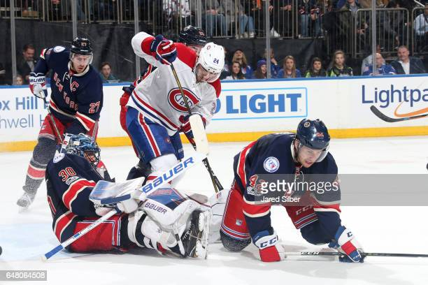 Henrik Lundqvist of the New York Rangers makes a save as Phillip Danault of the Montreal Canadiens looks for a rebound at Madison Square Garden on...